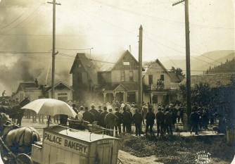 a 1903 house fire at the corner of Stanley and Mill looking east. The black horse on the right is a fire horse. The one pulling the bakery wagon may be a retired fire horse who couldn't resist answering the call. Courtesy of The BC Archives.